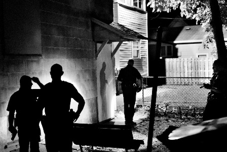 Several police officers search a house for an armed suspect in Northeast Rochester. Rochester, NY. USA 2012